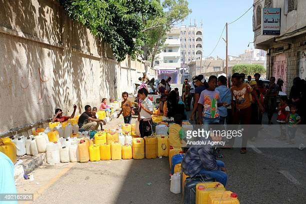 Children are seen near plastic cans as they wait to buy water in Taiz Yemen on October 10 2015 Because of the ongoing clashes there is water and food...