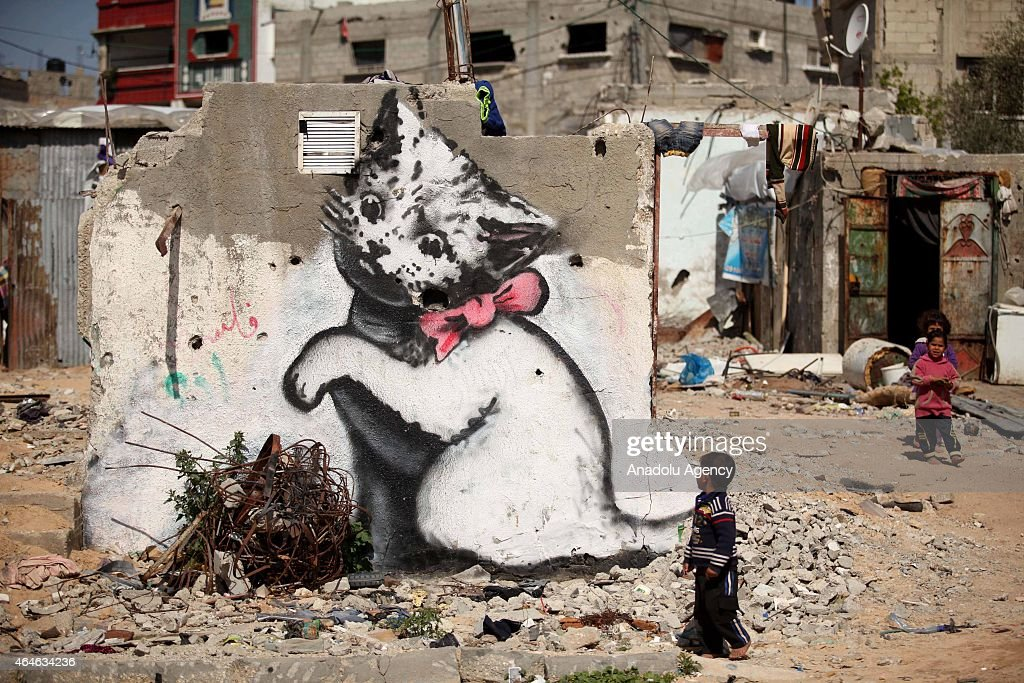 Children are seen near to a graffiti on a wall of a building drawn by British artist Banksy in Beit Hanoun, Gaza on February 27, 2015. Famous British artist Banksy visited Gaza and drew graffiti on the walls of houses in Beit Hanoun destroyed in Israel's recent attacks on Gaza.