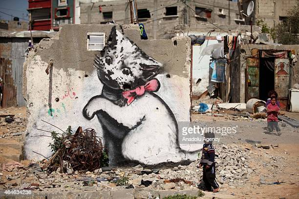 Children are seen near to a graffiti on a wall of a building drawn by British artist Banksy in Beit Hanoun Gaza on February 27 2015 Famous British...