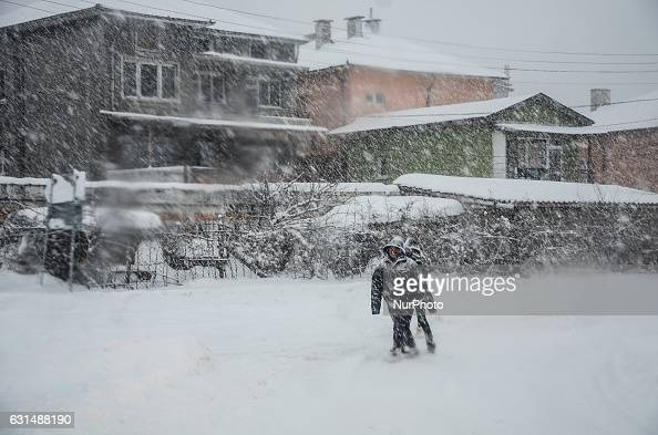 children are walking as snow falls at the streets of Svilengrad Bulgaria on January 11 2017 Snow paralyse Bulgaria The snow reached 40 70 sm at...