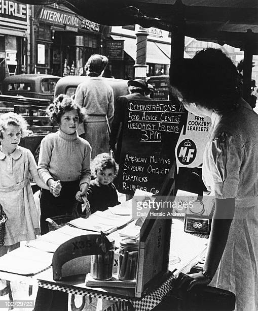Children at a Ministry of Food market stall World War Two 17 June 1944 'Mummy says will you please tell us which vegetables are best today and she...