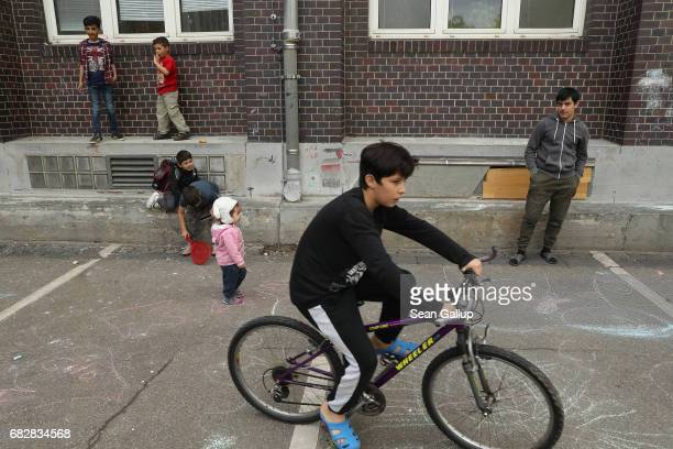 Children at a shelter for refugees and migrants in Marienfelde district play and pass time in the courtyard of the building on May 3 2017 in Berlin...