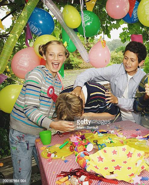 Children (9-12) at birthday party, boy pushing other's face into cake