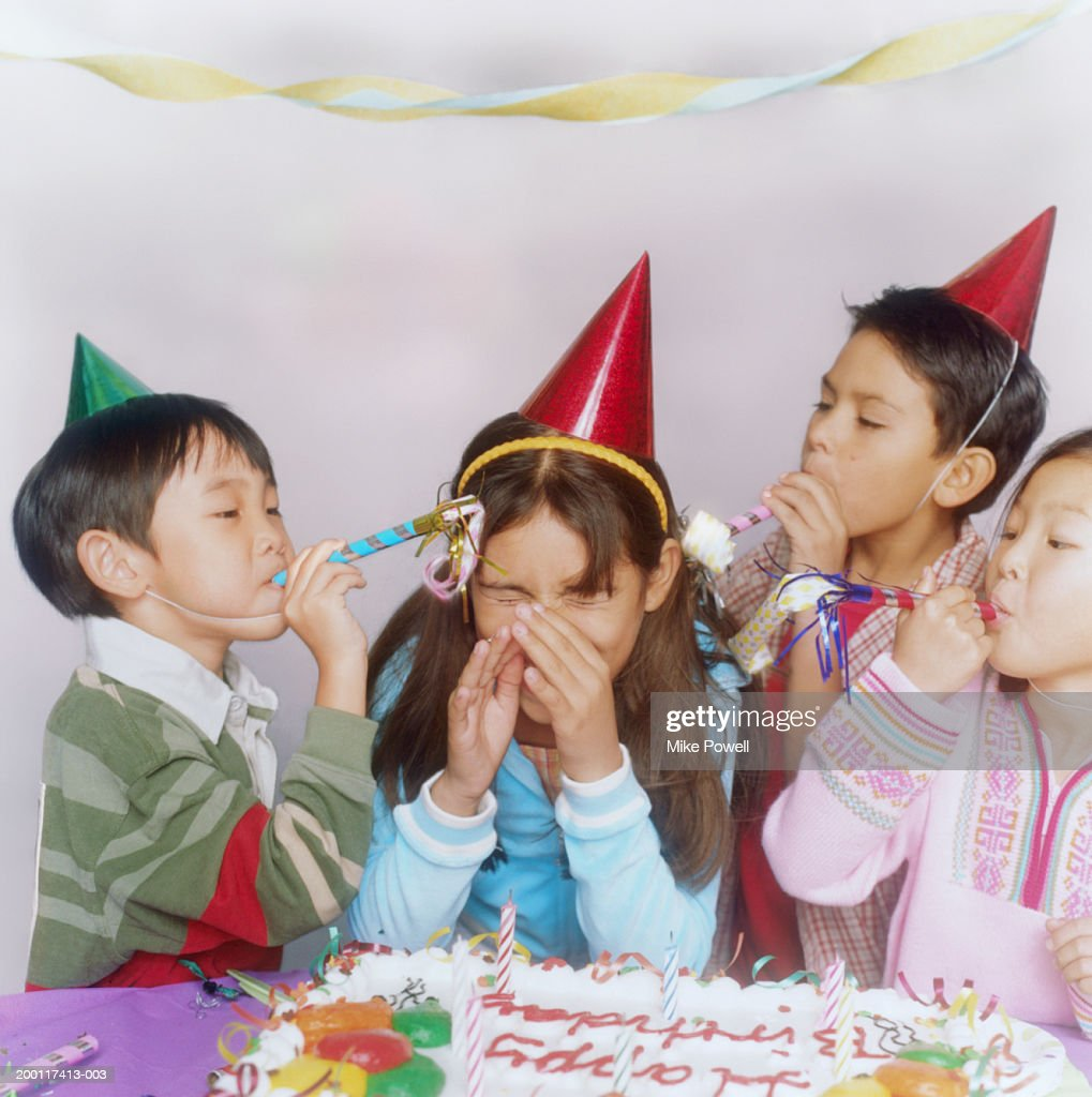 Children (6-10) at birthday party, playing with party favors : Stock Photo