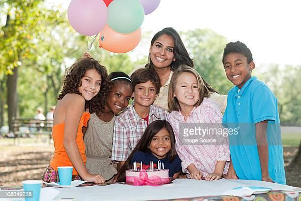 Niños en fiesta de cumpleaños con pastel de cumpleaños