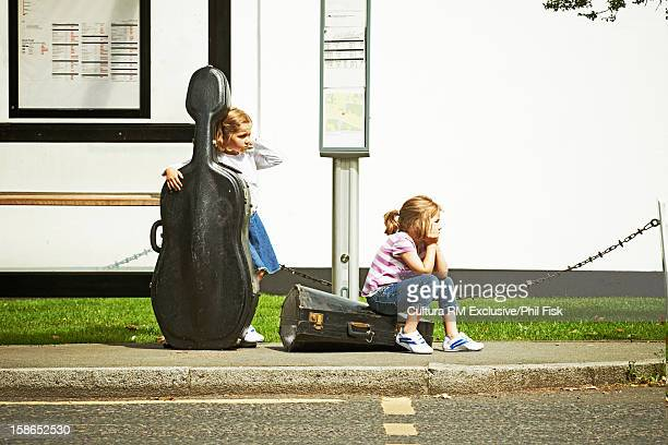 Children at bus stop with instruments