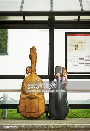 Children at bus stop with instruments : Stock Photo