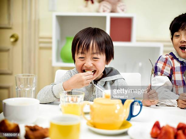 children at dining table, eating a breakfast.