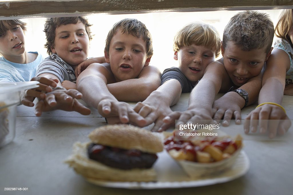 Children (6-10) at fastfood vendor's window, reaching for plate : Stock Photo