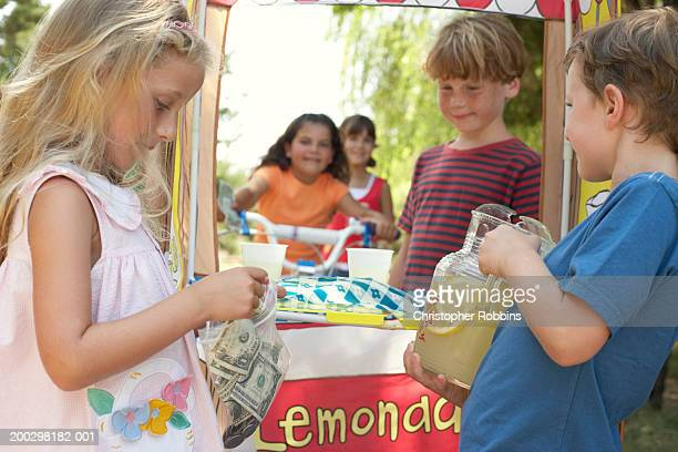 Children (6-12) at lemonade stall, girl (5-7) putting money in bag