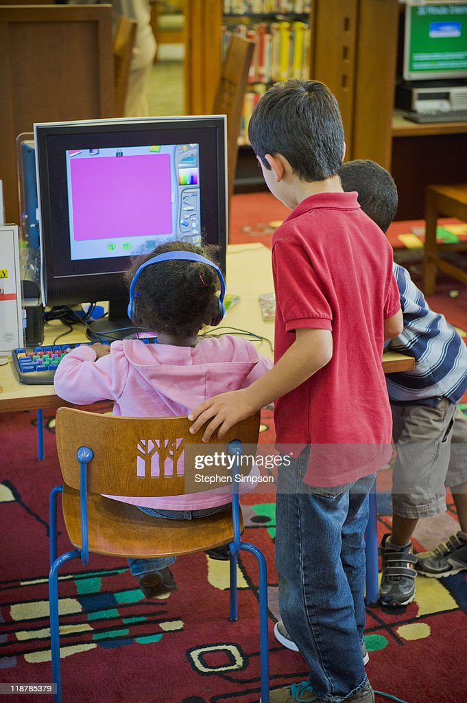 children at library computer desk : Stock Photo