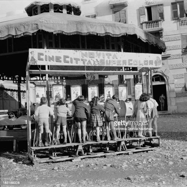 Children at Luna Park around the 'Casler's mutoscopes' a sort of motion picture device which simulates animation photographically Genoa Italy 1952...