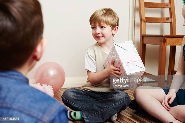 Children at party, boy holding birthday present