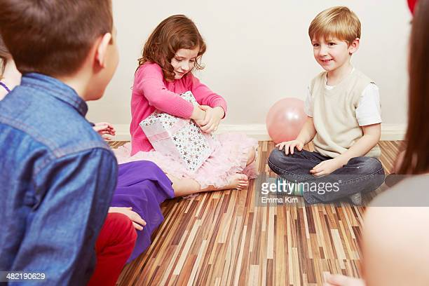 Children at party, girl holding birthday present