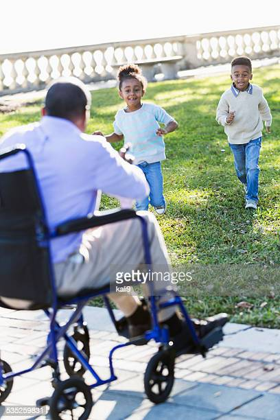 Children at the park running toward their grandfather
