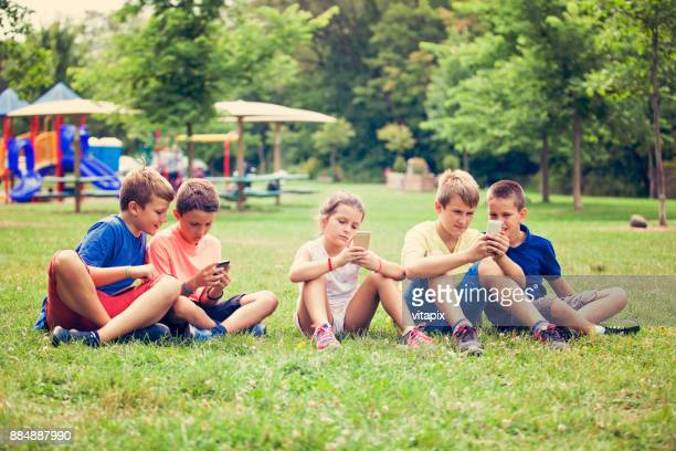 Children at the Park Using Mobile Phones Instead of Playing