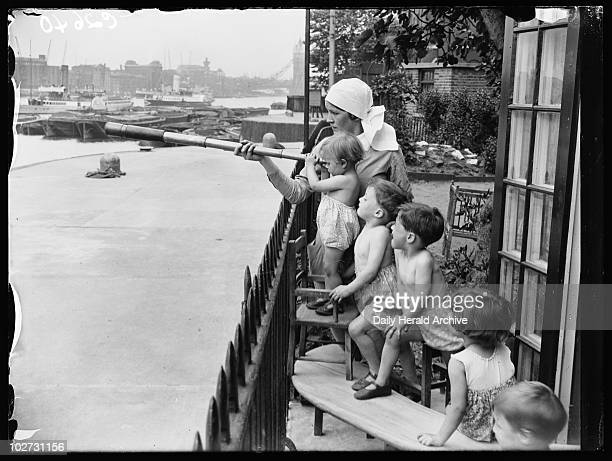 Children at the Port of London Day Nursery Wapping London 1933 A nursery nurse holds a telescope while children look out at the River Thames Tower...