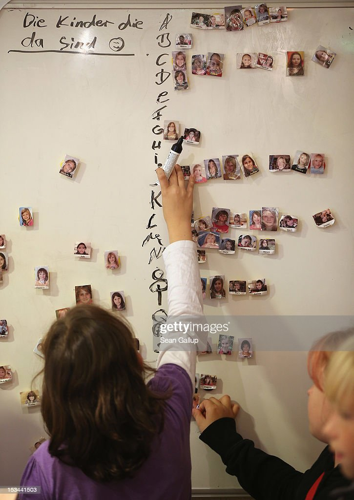 Children attach portraits of other children present that day on a magnet board at the 'Arche' youth center in Marzahn-Hellersdorf district on October 5, 2012 in Berlin, Germany. The Arche (which means Ark) is a Christian-based facility that provides children of all ages with a hot lunch, help with homework, arts and play facilities and in general a welcome place to come to in Marzahn-Hellersdorf district in east Berlin, a district with high levels of unemployment and social problems. An employee said up to 90% of the children come from challenged families and that many arrive at Arche illiterate.