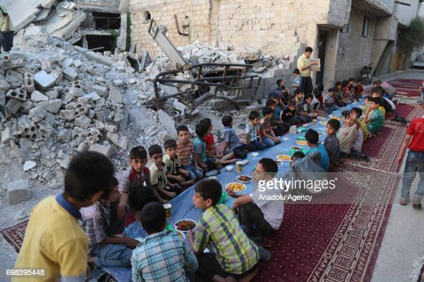 Children attend an iftar dinner organized by Adale Relief Foundation around the debris of buildings at Douma district which is under blockade for...