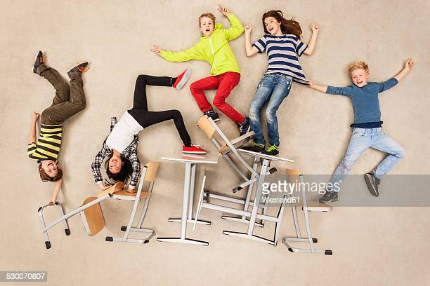 Children balancing on school chairs