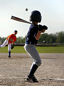 Kids playing baseball in game.  Batter is waiting for pitch in air released from pitcher.