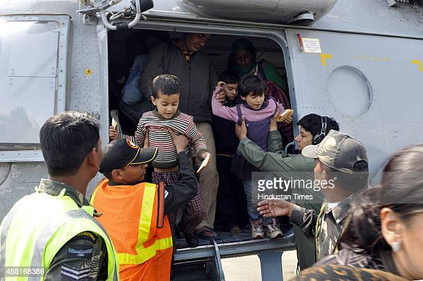 Children being taken out of IAF helicopter by Indian Air Force personnel after a rescue operation at the airport on September 10 2014 in Srinagar...