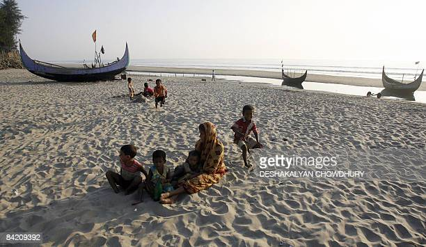 Children belonging to a Bangladeshi fisherman family play with their mother at the beach in Cox's Bazar district of Chittagong on January 7 2009...