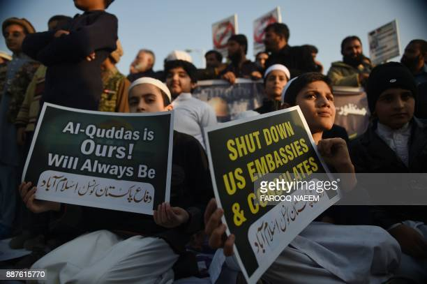 Children belonging to the Defence of Pakistan Council hold placards during an antiUS and Israeli protest in Islamabad on December 7 2017 following...