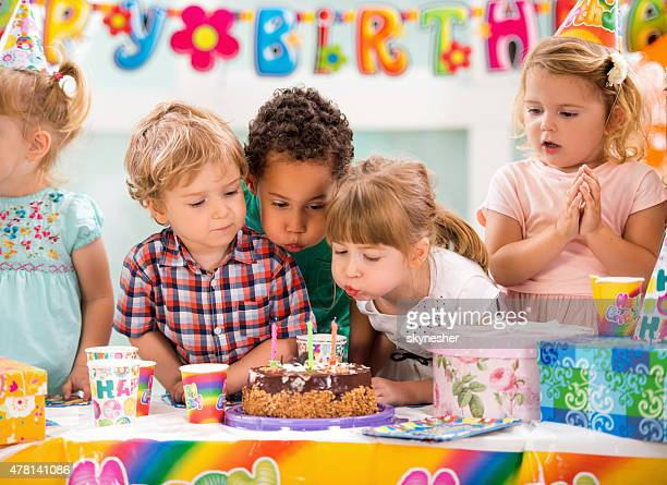 Crianças de aniversário a soprar as velas na festa de aniversário.