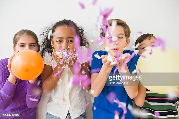Children blowing party confetti and balloons