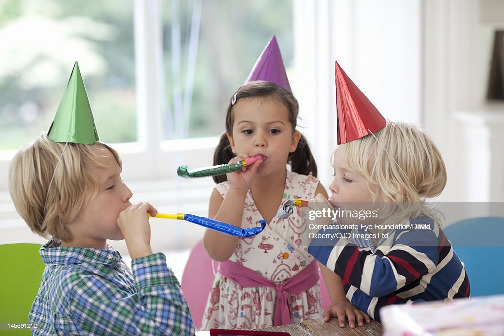 Children blowing party horn blowers : Stock Photo