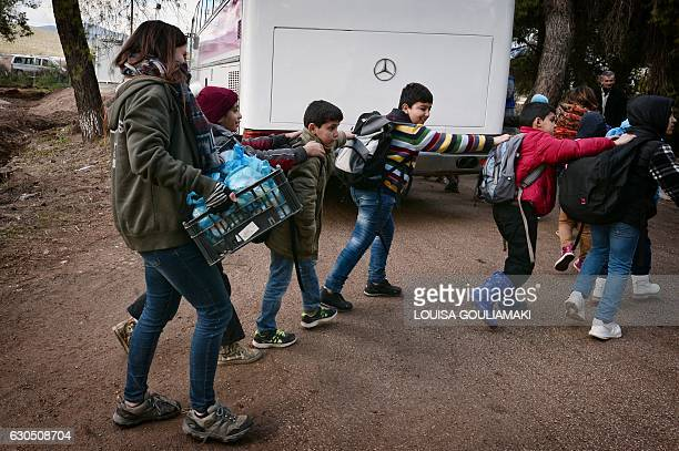 Children board a bus to get to school as volunteer holds a crate with sandwiches prepared in camps's 'cafe Rits' in Ritsona refugee camp some 80 km...
