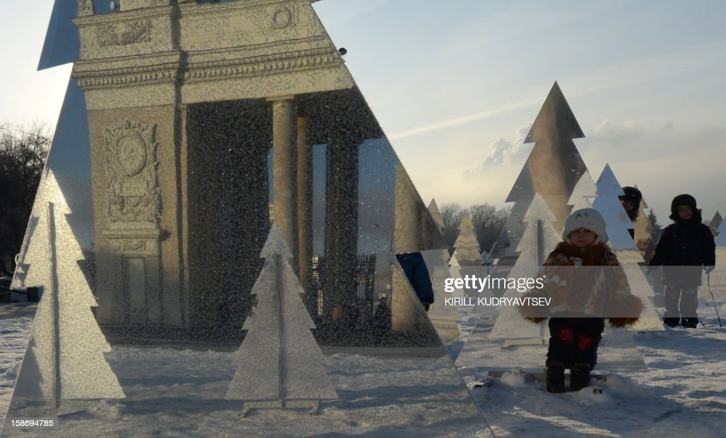 Children brave the freezing outdoors while waiting for the arrival of Ded Moroz (Grandfather Frost), the Russian Santa Claus, at the entrance to Moscow's Gorky Park, on December 24, 2012, The arch at the main entrance to Gorky Park is reflected in a polished surface of an artificial New Year tree. The temperatures in Moscow dropped today to -22C (-7F), but due to high humidity and strong cold wind, weather experts said it would feel more like -26C (-14F).