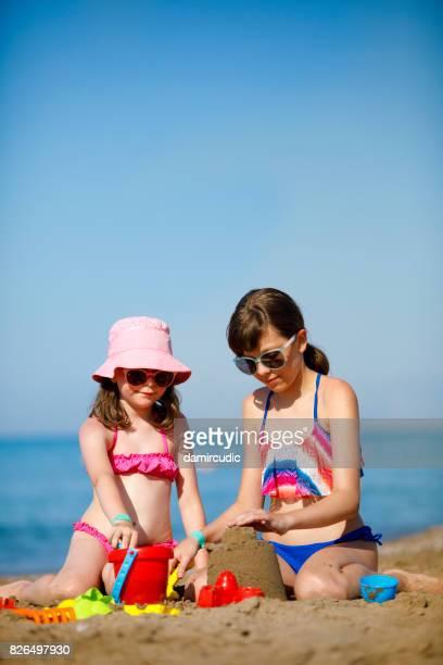 Children building a sandcastle on the beach