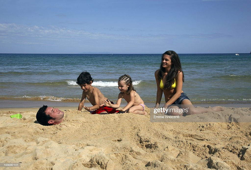 children burying dad in the sand