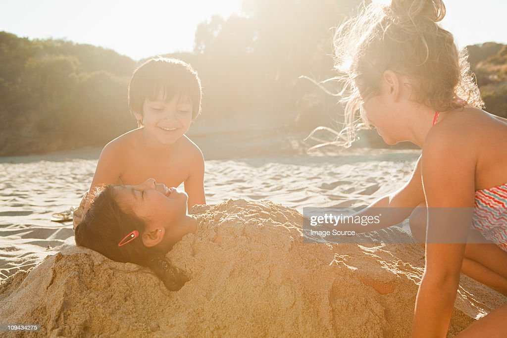 Children burying girl in sand