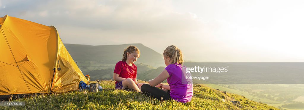 Children camping on green summer mountain overlooking sunlit valley panorama
