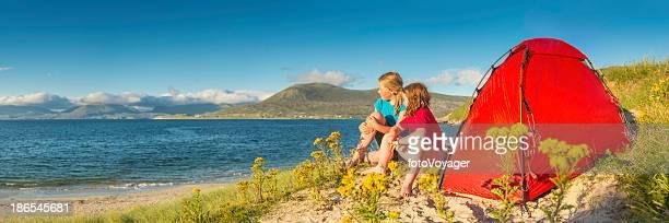 Children camping on idyllic golden beach dunes summer ocean panorama
