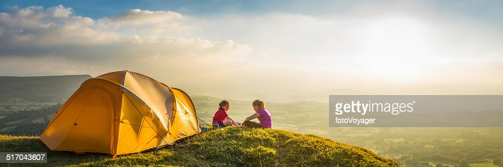 Children camping on idyllic summer sunset mountain light panorama