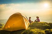 Children camping yellow tent on idyllic mountain top summer sunset