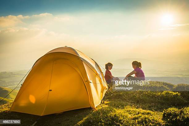 Children camping yellow tent on idyllic mountain top summer sunset