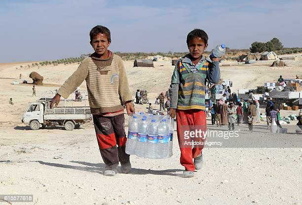 Children carries the aid packages sent by Humanitarian Aid Foundation at new village which was established near Sajur River by the Syrian civilians...