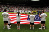 Children carries the national flag of USA foregrounds the USA and New Zealand team during the prematch ceremony during the Women's Football Quarter...
