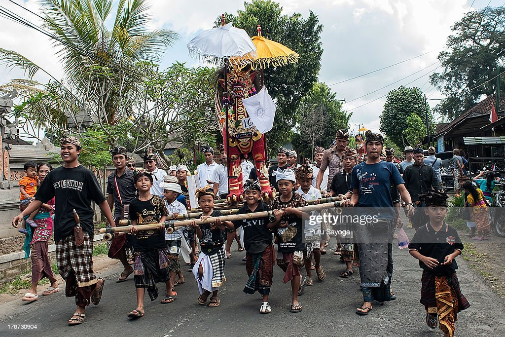 Children carry a sarcophagus to the cremation site during a Balinese Hindu mass cremation on August 18, 2013 in Ubud, Bali, Indonesia. More than 60 corpses were collectively cremated to share the expense of the ceremony. Well known as Ngaben, it is one of the most important ceremonies for Balinese Hindu people, as they believe it will free the spirit from the deceased body so it can reincarnate.