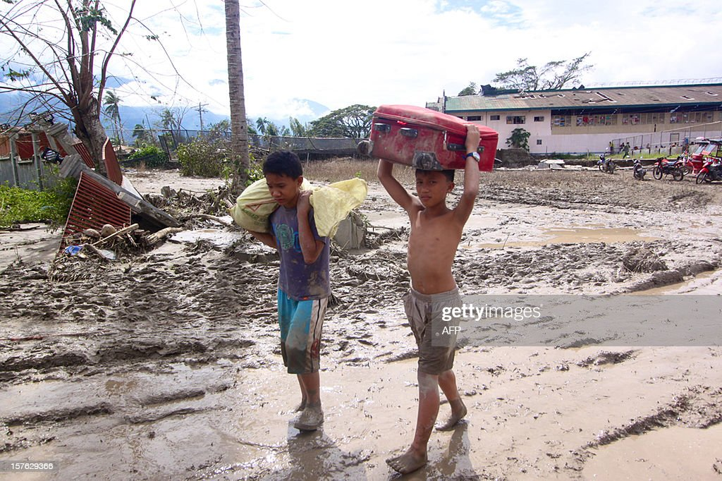 Children carry beloingings along a muddy street in the aftermath of Typhoon Bopha in New Bataan, Compostela Valley in the southern Philippines on December 5, 2012. The death toll from a typhoon that ravaged the Philippines jumped to 238 on December 5 with hundreds missing, as rescuers battled to reach areas cut off by floods and mudslides, officials said. AFP PHOTO / Karlos Manlupig