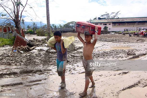 Children carry beloingings along a muddy street in the aftermath of Typhoon Bopha in New Bataan Compostela Valley in the southern Philippines on...