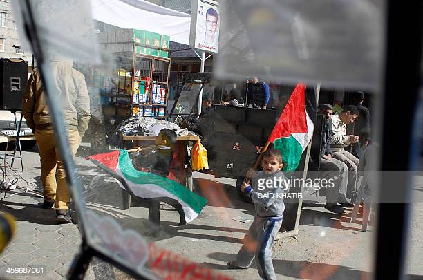 Children carry the Palestinian flag as they prepare for the release of prisoner Ramy Barbakh outside his home in Khan Yunis in the southern Gaza...