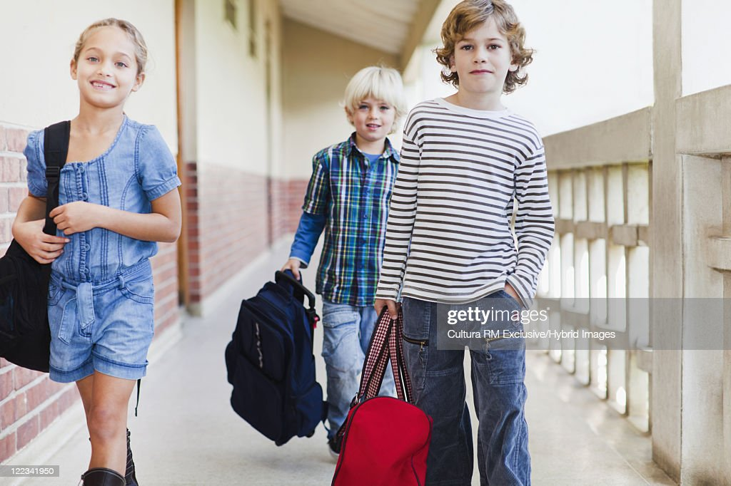 Children carrying backpacks at school : Stock Photo