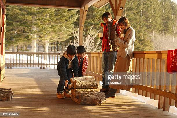 Children carrying firewood and parents standing by watching
