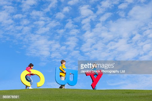 Children carrying large letters in field